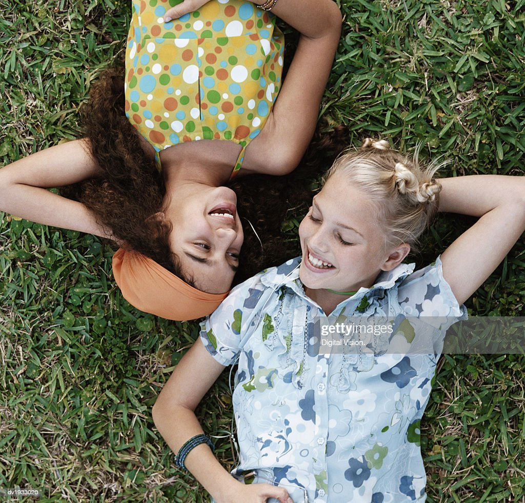Teenage Girls Face to Face Lying on Grass : Stock Photo