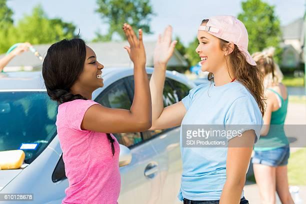 Teenage girls give high fives during car wash
