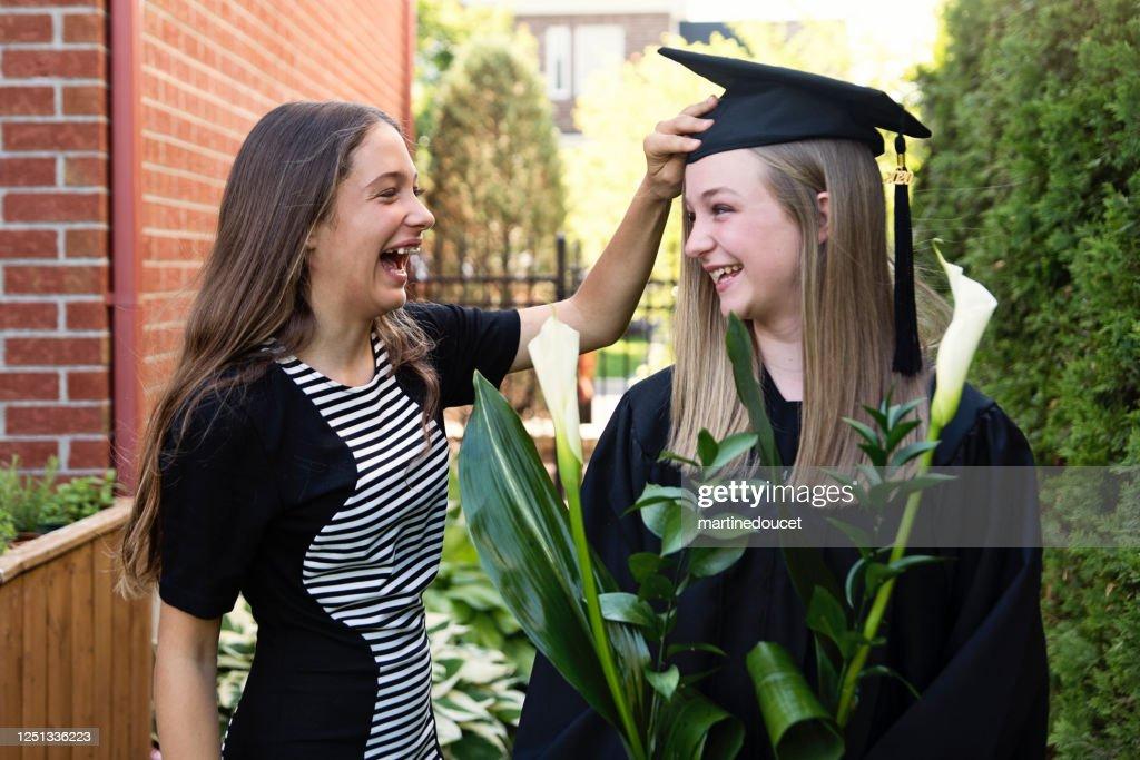 Teenage girls graduation from primary school portrait in backyard. : Stock Photo