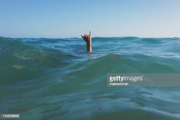 Teenage girls hand coming out of the ocean making a Hang Loose sign
