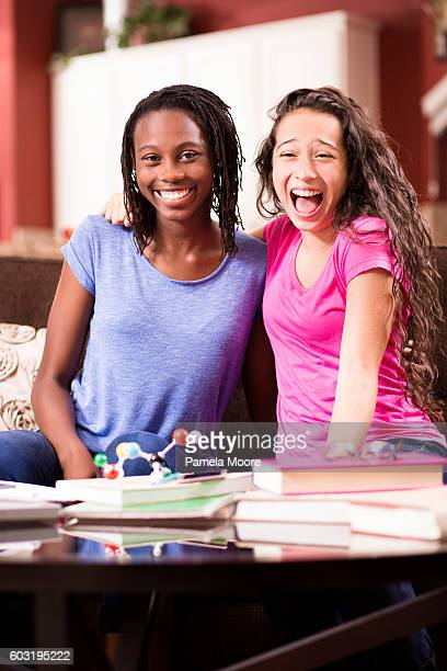 Teenage girls have fun studying science at home.