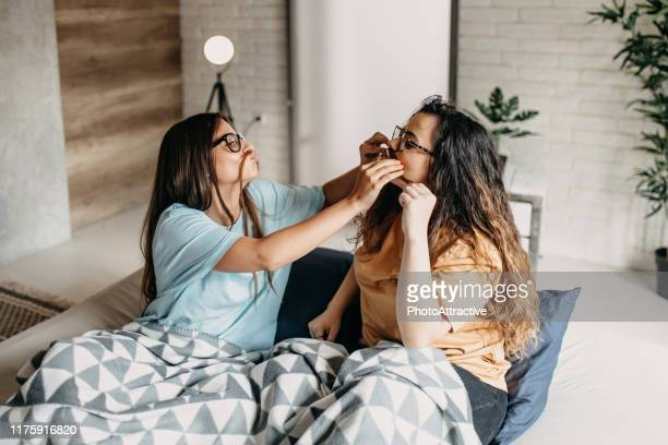 teenage girls having fun in bed - sibling stock pictures, royalty-free photos & images