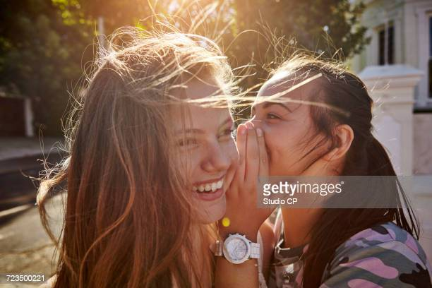 teenage girls having fun in residential street, cape town, south africa - whispering stock pictures, royalty-free photos & images