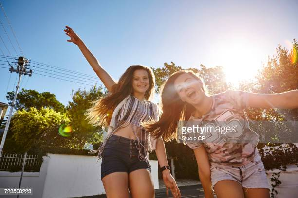teenage girls having fun in residential street, cape town, south africa - クロップトップ ストックフォトと画像