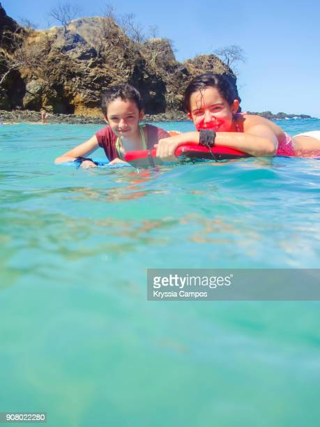 teenage girls having fun on surfboard in the sea - lanzarote stock pictures, royalty-free photos & images