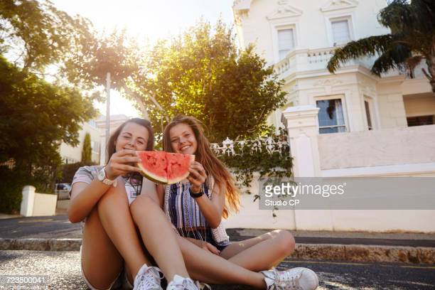 Teenage girls having watermelon in street, Cape Town, South Africa