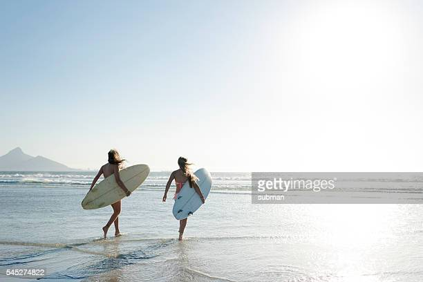 Teenage Girls Heading Out To Surf