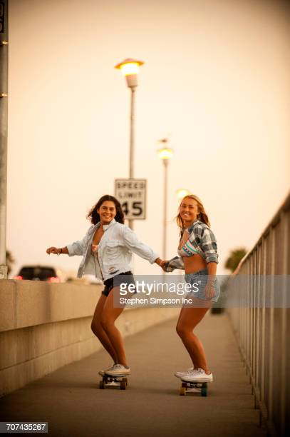 Teenage girls holding hands while riding skateboards