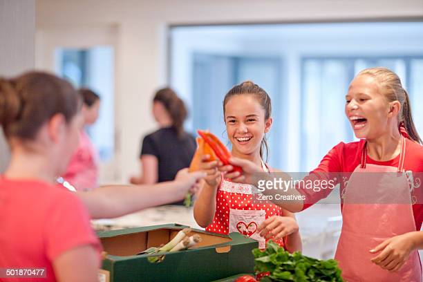 Teenage girls holding up chillies and carrot in kitchen