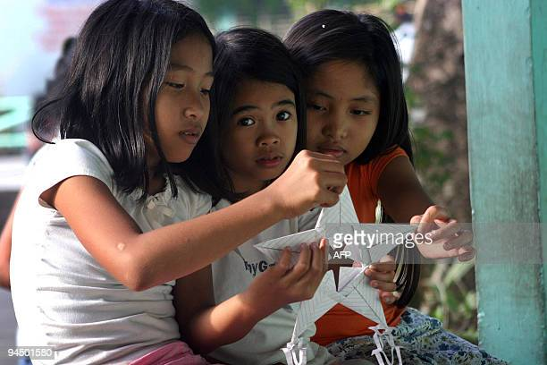 Teenage girls huddle as they look at an improvised lantern at an evacuation center in Legazpi City Albay province southeast of Manila on December 16...
