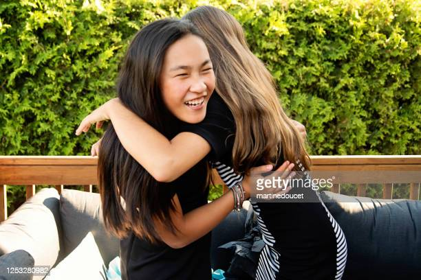 """teenage girls hugging during backyard party. - """"martine doucet"""" or martinedoucet stock pictures, royalty-free photos & images"""