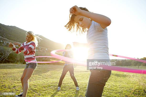 Teenage girls hula-hooping together