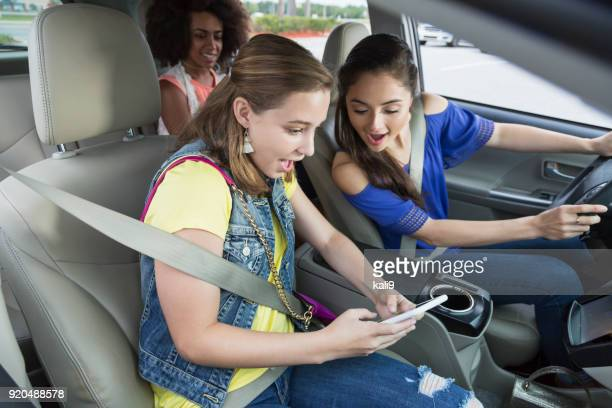 mädchen im teenageralter in auto, lachen, handy - abgelenkt stock-fotos und bilder