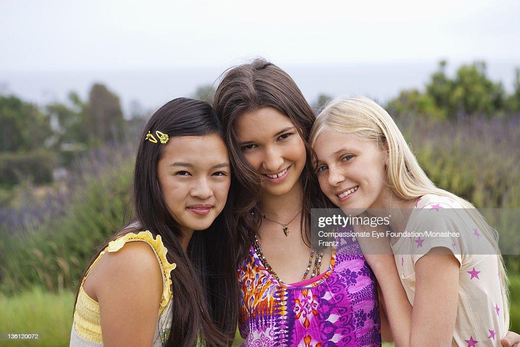 Teenage girls in garden, portrait, smiling : Stock Photo