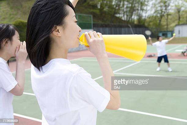 Teenage girls in gym clothes cheering boys playing tennis, one holding a megaphone