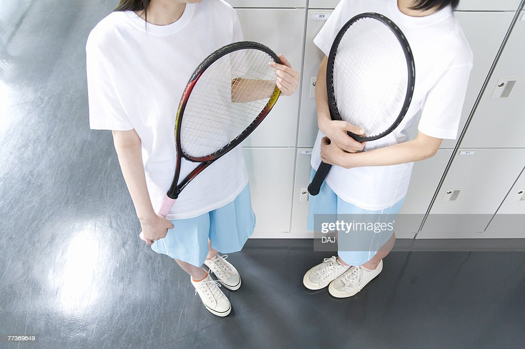 Teenage girls in gym clothes holding tennis rackets in locker room : Stock Photo