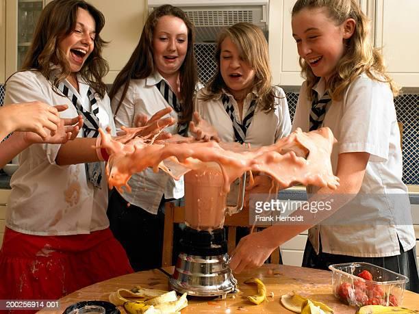 Teenage girls (13-15) in kitchen, milkshake exploding from blender