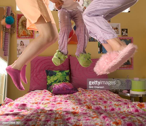 Teenage girls (13-17) in nightwear jumping on bed, low section