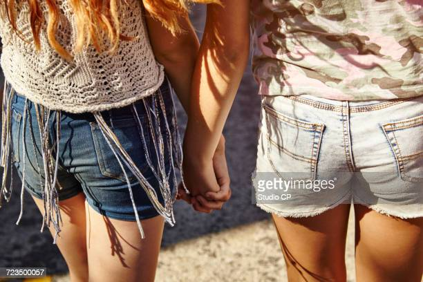 teenage girls in street, rear view of shorts and hands - denim shorts stock pictures, royalty-free photos & images