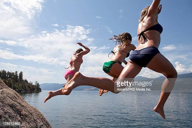 Teenage girls jump of rock cliff into lake below