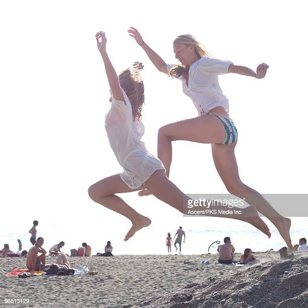 Teenage girls jump off sand pile, at busy beach
