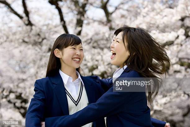 Teenage girls jumping and smiling under cherry trees, front view, side view, Japan