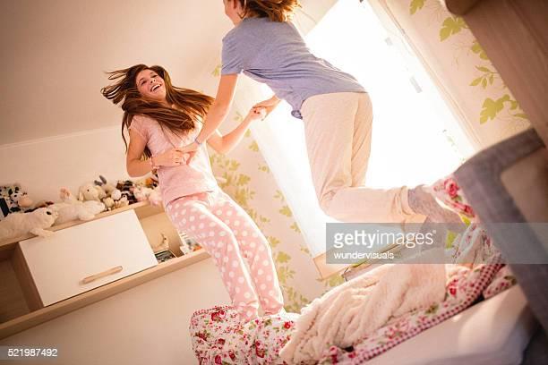 Adolescentes Chicas salto alrededor de juntos en una cama en pijama