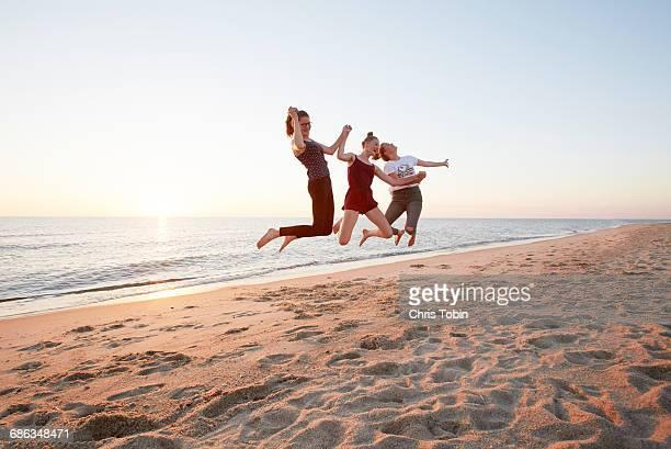 teenage girls jumping at beach - schleswig holstein stock-fotos und bilder