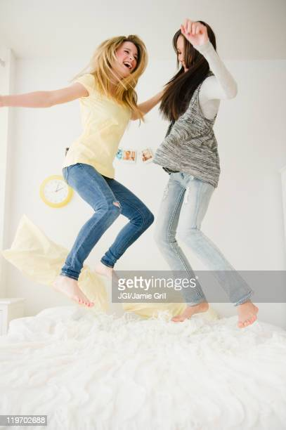 Teenage girls jumping on bed together