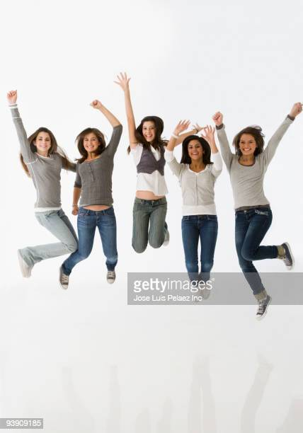Teenage girls jumping with arms raised
