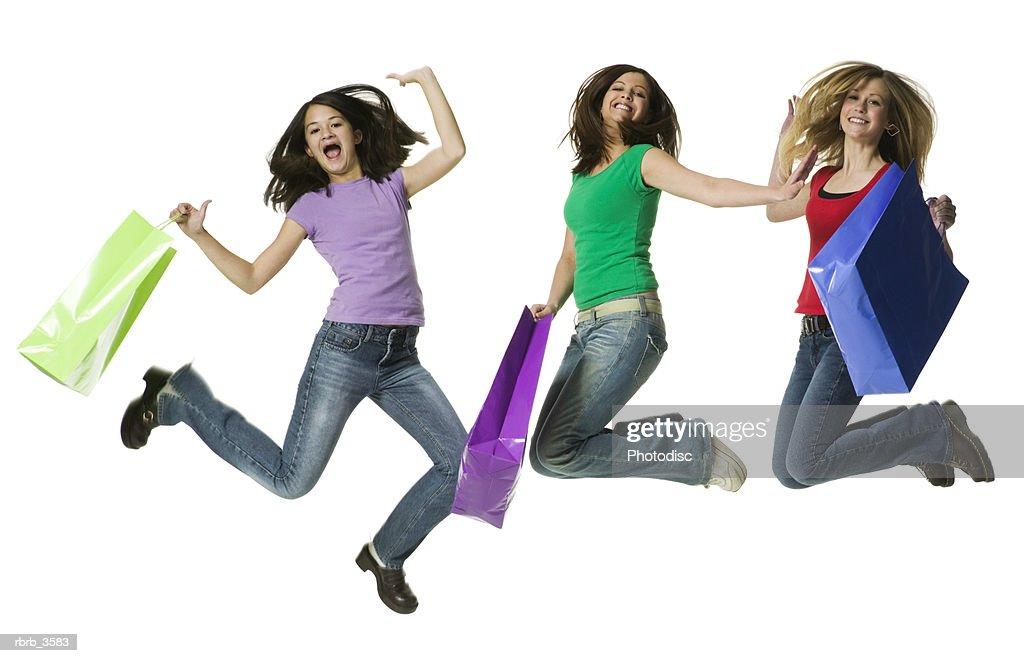 Teenage girls jumping with shopping bags : Foto de stock