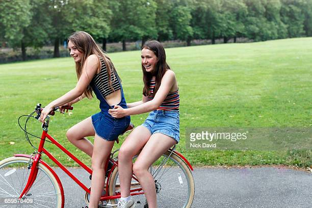 teenage girls laughing on a bike together - only teenage girls stock pictures, royalty-free photos & images