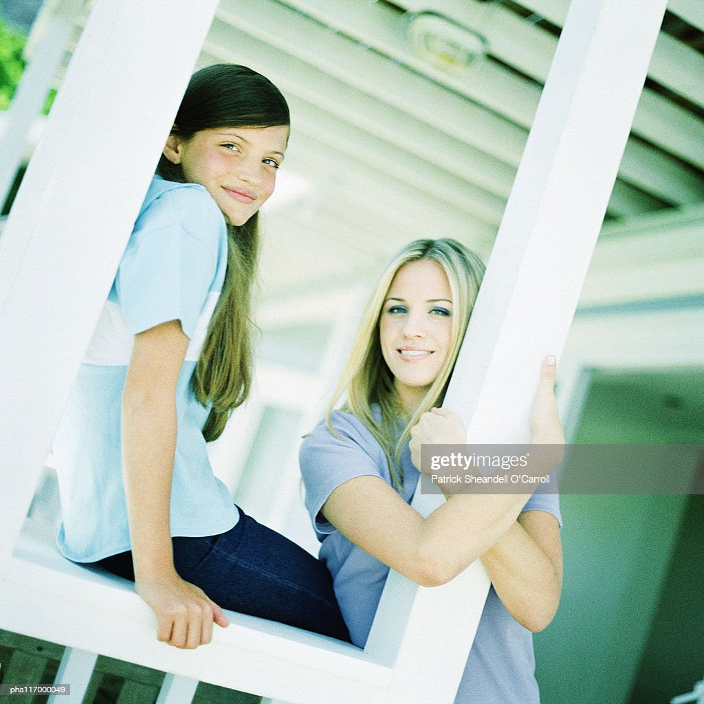 Teenage girls leaning against posts on porch : Stock Photo