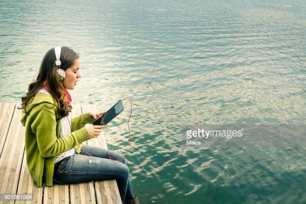 Teenage girls listening music in riverside