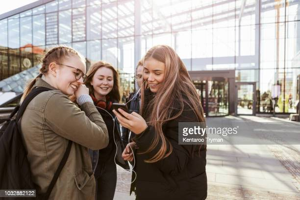 teenage girls listening music through mobile phone while standing with friends outside railroad station - seulement des adolescents ou adolescentes photos et images de collection