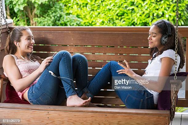 Teenage girls listening to music on porch swing