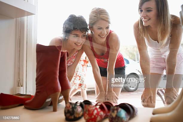 Teenage girls looking at shoes on window display
