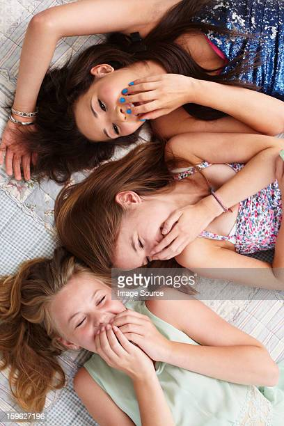 Teenage girls lying on bed and giggling