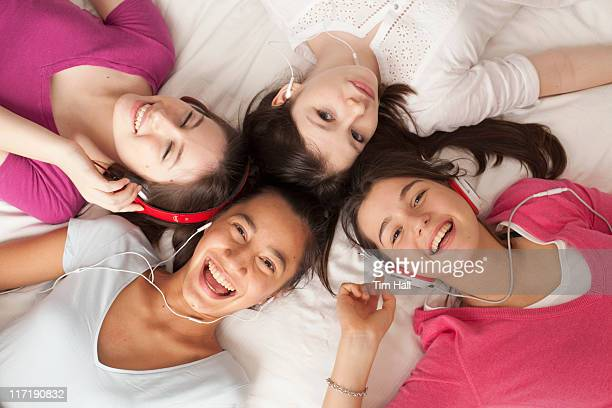 teenage girls lying on floor listening to music, smiling