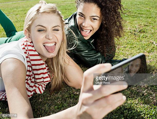 Teenage girls (13-15, 16-17) lying on meadow and photographing themselves