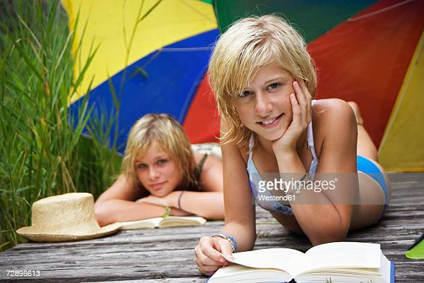Teenage girls (13-15) lying under sunshade on jetty, reading book, close-up