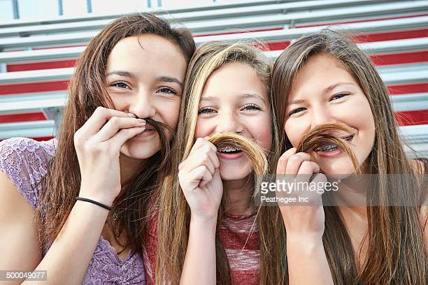 Teenage girls making fake mustaches with hair