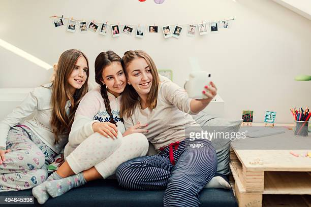 Teenage Girls Making Selfie With Instant Camera.