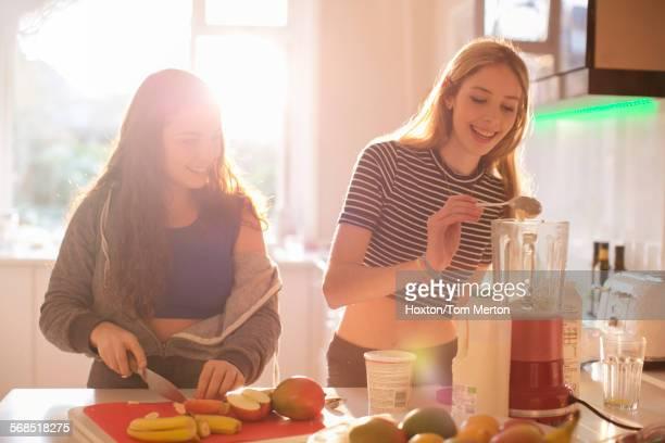 Teenage girls making smoothie in sunny kitchen