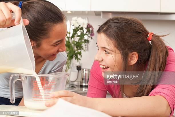 teenage girls measuring milk in kitchen