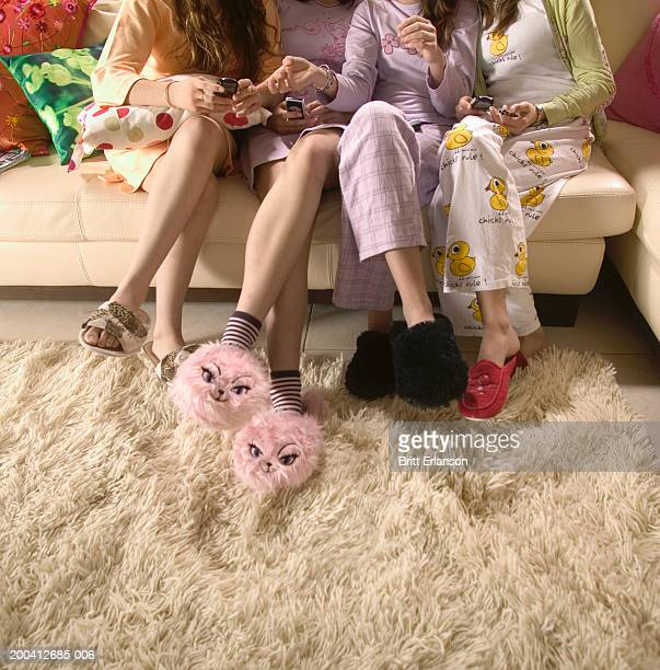 teenage girls (12-17) on sofa, holding mobile phones, low section - slumber party stock pictures, royalty-free photos & images