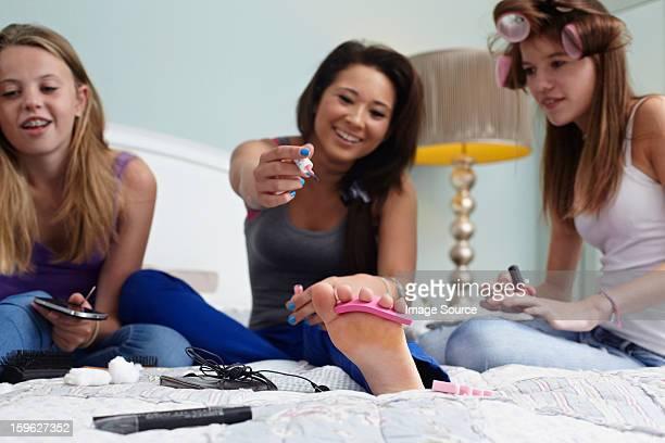 Teenage girls painting toenails