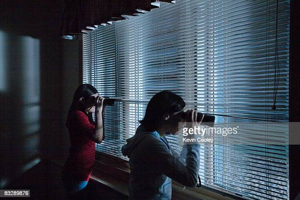 Teenage girls peering out bedroom window