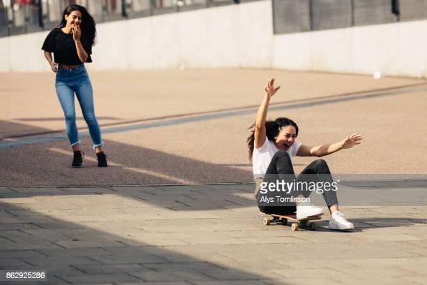 Teenage girls playing around on skateboard