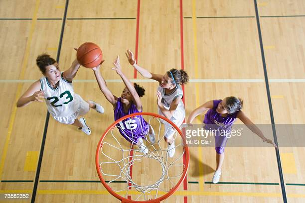 Teenage girls (16-19) playing basketball, elevated view